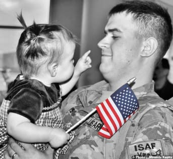Photo of soldier with little girl by Miranda Keatts