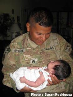 Photo of soldier holding baby by Susan Rodriguez