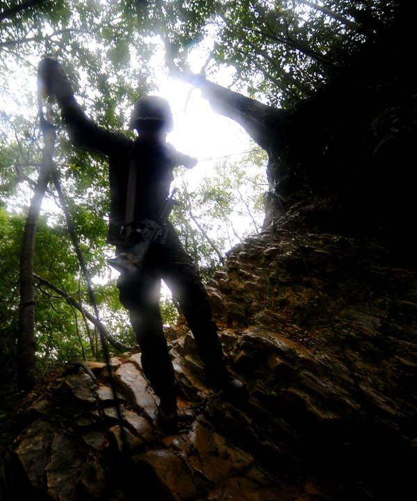 A Seabee rappels down a steep cliff wall during jungle warfare training