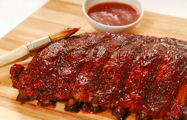 Slab of freshly grilled BBQ spare ribs with dipping sauce