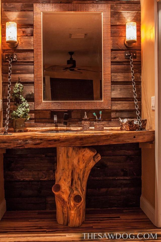 Here is a custom bathroom vanity I built with a cedar base holding up cypress live edge counter top with hammered copper sink and pallet wood wall and onyx light fixtures