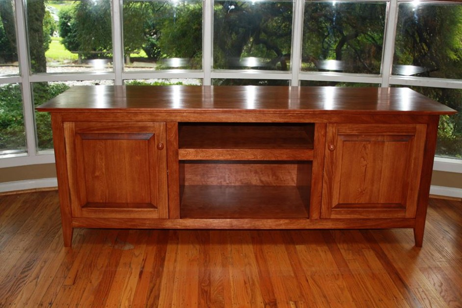 A Shaker inspired case piece in cherry. Raised panels in front and on the sides and there is a drawer behind each door.
