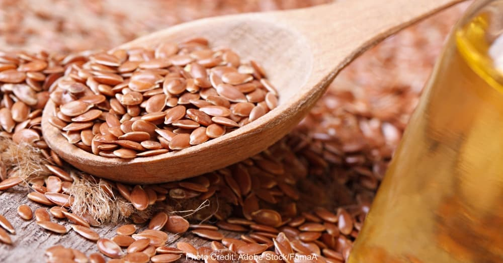 Flax seed in a spoon and oil. horizontal