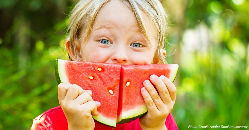 Funny happy child eating watermelon outdoors