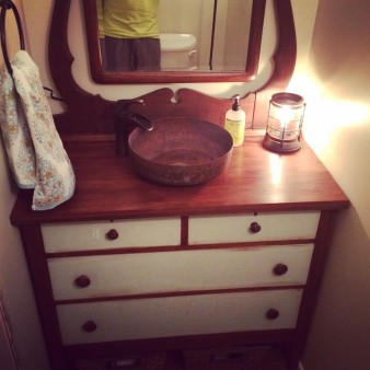 This bathroom vanity was created from a dresser that belonged to my great aunt. The copper bowl turned sink was purchased from a peddler mall and I cut it for the drain and plumbing.