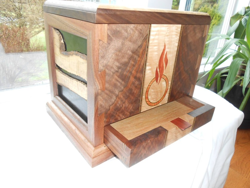 Urn made for my brother that passed away last January.  Made of Vancouver island Claro walnut, Vancouver island big leaf Maple, and bloodwood. There is a small drawer for letters and i also made a hollow in the base that my wife and i put letters in a sealed it up forever.