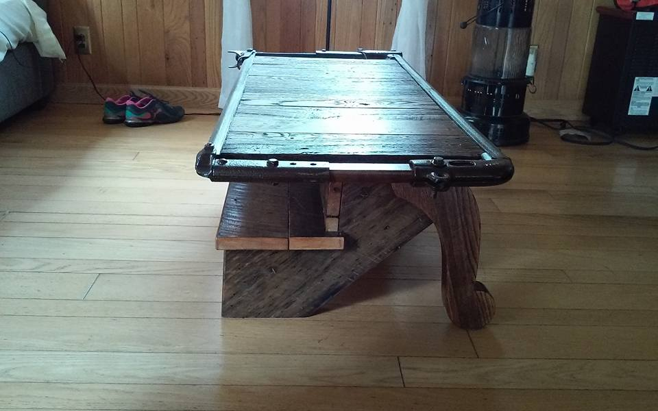 Hers our new coffee table made from barn wood , old stair stringer , old legs off of a antique table and a cattle stanction ,, headgate,, found in the barn , everything is probably 100 years old or better lol