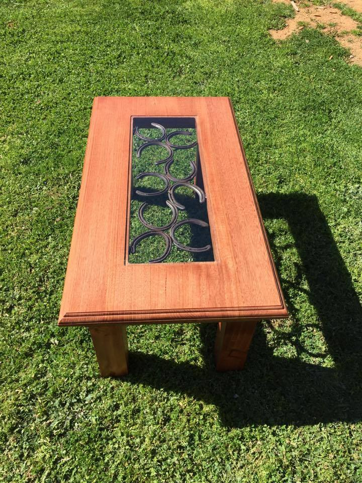 From Jemma Corbett: Coffee table I made. Top is Tasmanian oak and base is pine. Jarrah stain. 2pac lacquer. Horseshoe and glass inlay.