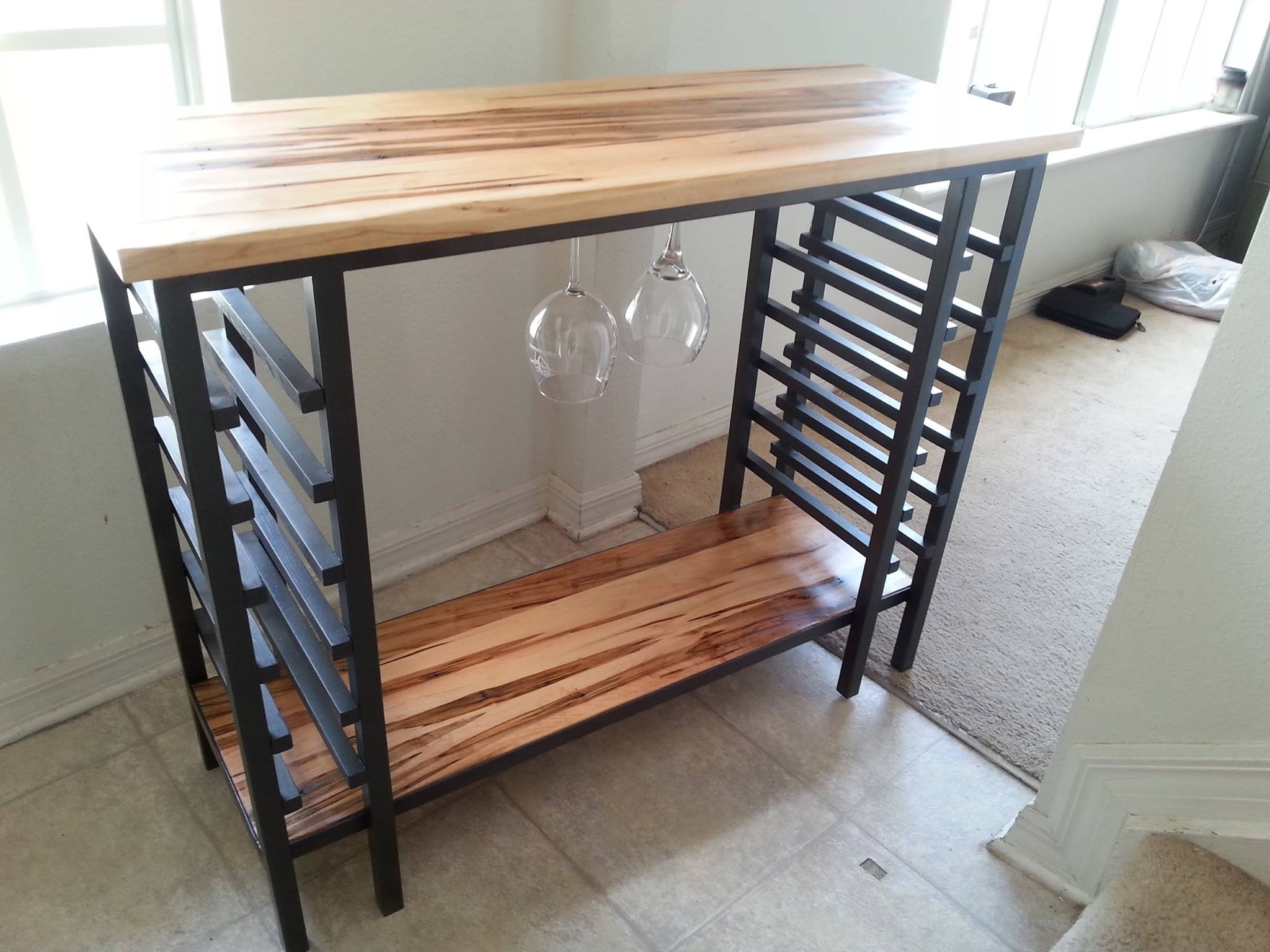 From Nick Lyman: It is a custom wine rack made as a wedding gift for my sister.  The frame is welded steel and the surfaces are Ambrosia Maple finished with true tung oil.  It holds 12 wine glasses in hangers and 12 wine bottles in the vertical racks.