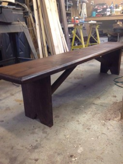 From Jeff Owens: Black walnut bench modeled after a old west church pew I saw in a movie 7'x15x18.25 By jeff Owens at holly meadows wood works parsons wv.