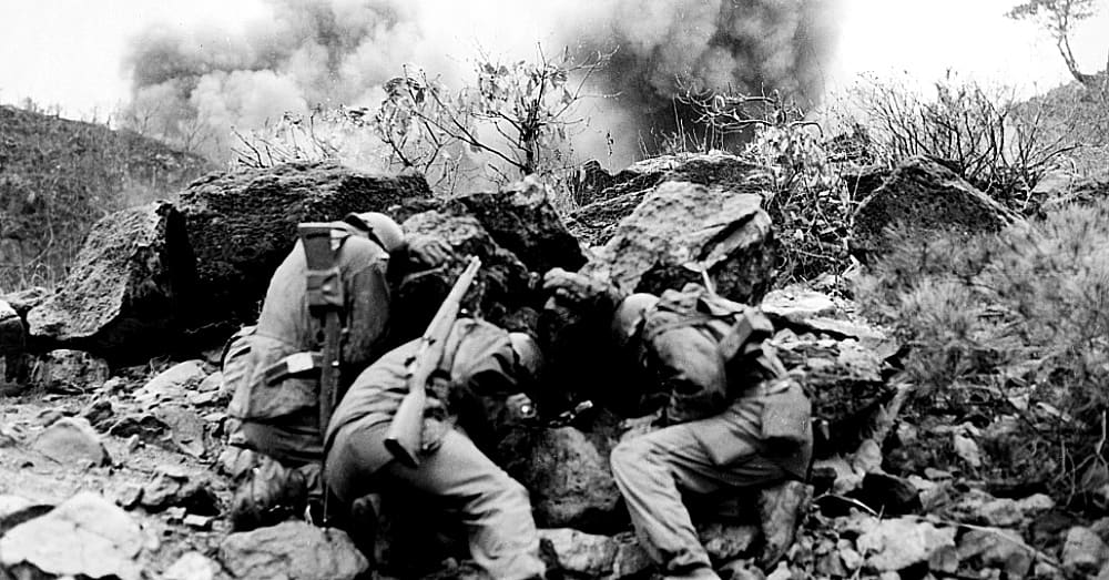 Men of the 3rd Battalion, 34th Infantry Regiment, 35th Infantry Division, covering up behind rocks to shield themselves from exploding mortar shells, near the Hantan River in central Korea / Via The Library of Congress