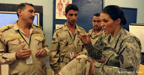 U.S. Army Spc. Sara Lenzo (right), a combat medic with Charlie Company, 225th Brigade Support Battalion, 2nd Advise and Assist Brigade, 25th Infantry Division, teaches Iraq soldiers how to splint a broken leg.