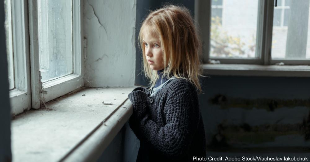 Depressed poot girl standing near window