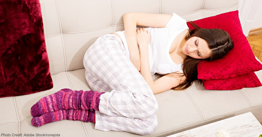Young woman in the sofa with period pain