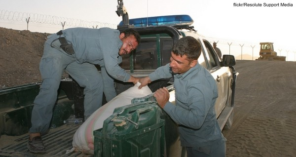 Afghan Uniformed Police unload the last bag of poppy seed from a seizure at a burn pit on Forward Operating Base Delaram 2, July 22.
