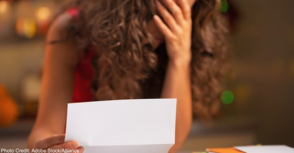 Closeup on stressed woman reading letter
