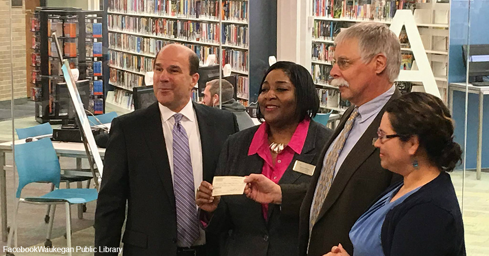Library Board members receiving the donation check at the Waukegan Public Library / Via Waukegan Public Library