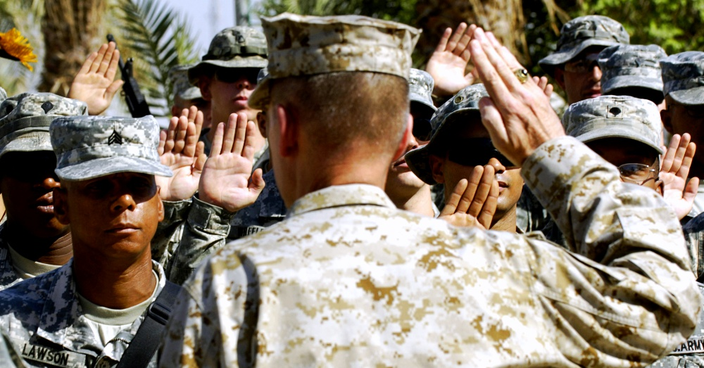 Marine Gen. Peter Pace gives the oath of enlistment to U.S. Army Soldiers during a re-enlistment ceremony at Camp Liberty, Iraq, 2007. Via The U.S. Army and Staff Sgt. D. Myles Cullen, U.S. Air Force
