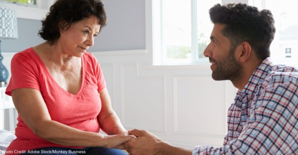 Adult Son Comforting Mother Suffering With Dementia