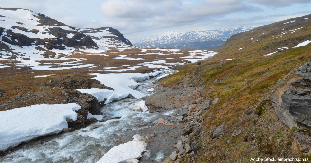 River with melting snowpatches in mountain valley, Swedish Lapland