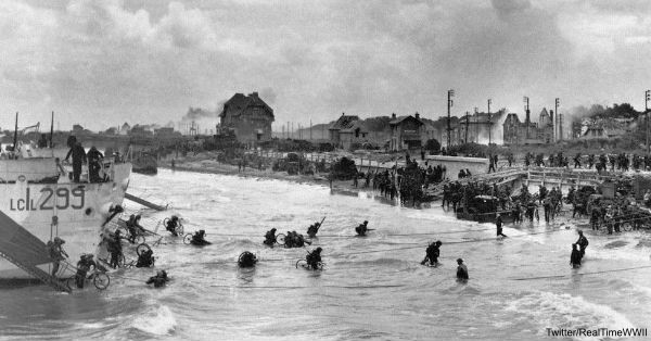 Canadian soldiers of 9th Brigade landing on Juno beach, carrying bicycles to speed their advance inland.