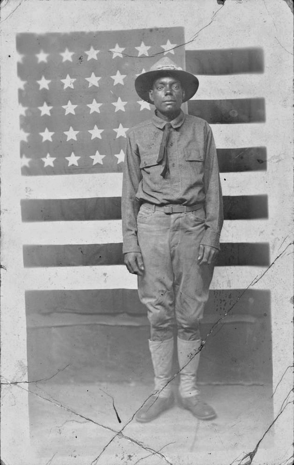 WWI soldier in uniform standing in front of American flag.