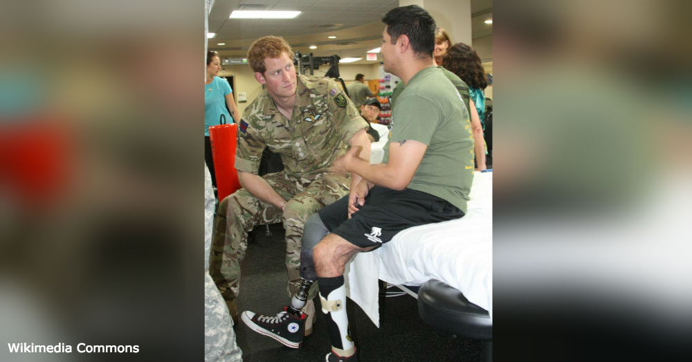 Prince Harry speaks with a wounded veteran.
