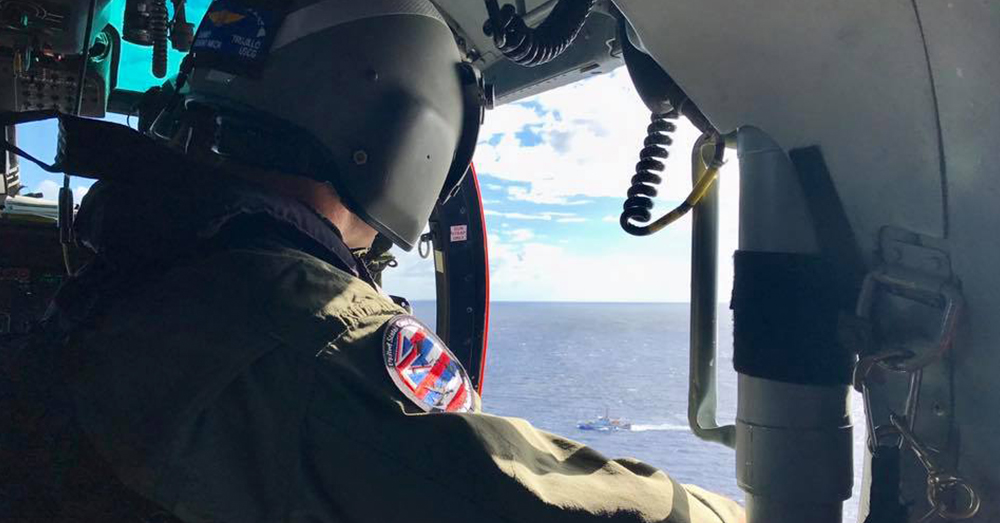 Photo: U.S. Coast Guard/Air Station Barbers Point -- An aircrewman scans the waters off Oahu for any sign of the five missing soldiers.