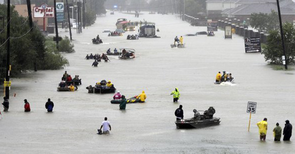 Photo: Twitter/The Associated Press -- Citizens of Houston make their way down a flooded street in the wake of Hurricane Harvey.