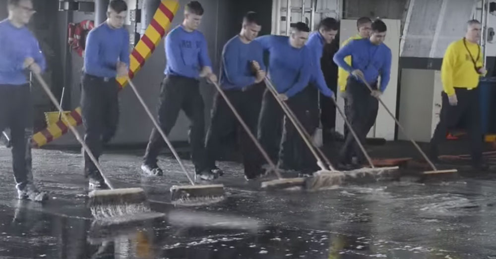 Source: YouTube/AiirSource Military A deck of the USS Harry S. Truman gets a good swabbing.