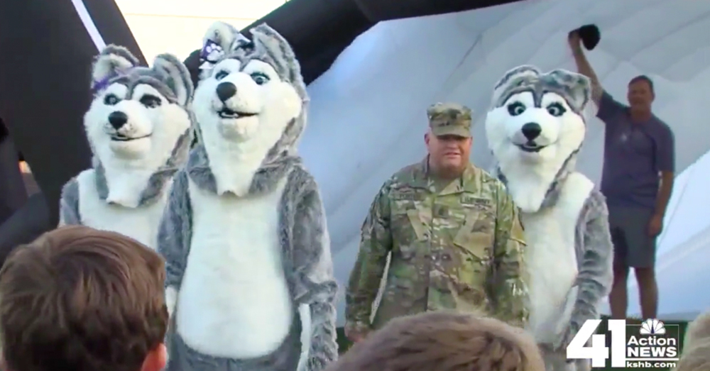 Photo: 41 KSHB screenshot -- First Sgt. Charles Porter hides with the mascots before the game.
