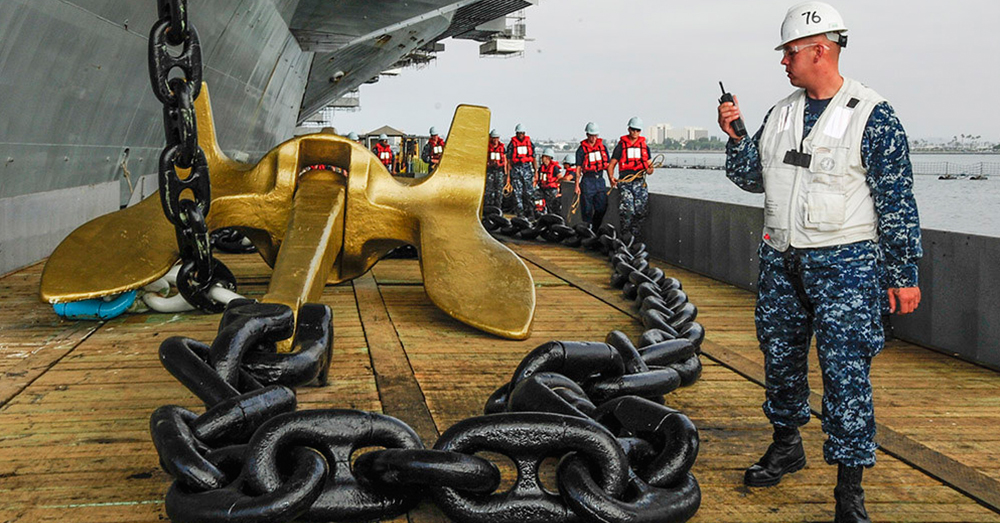 Photo: U.S. Navy/Mass Communication Specialist 3rd Class Timothy Schumaker -- Chief Warrant Officer 2 Michael Cowlishaw leads the raising of an anchor of the aircraft carrier USS Ronald Reagan.
