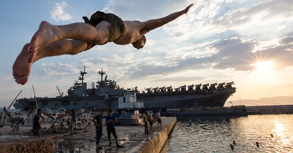 Photo: U.S. Navy/Mass Communication Specialist 2nd Class Corbin J. Shea -- A Marine from the 26th Marine Expeditionary Unit dives near the amphibious assault ship USS Kearsarge (LHD 3) during a swim call after the conclusion of Exercise Eager Lion.