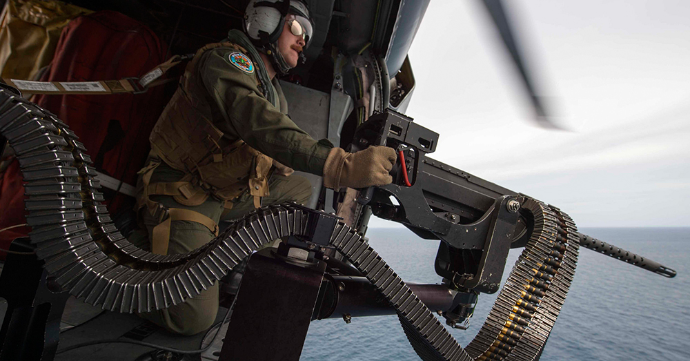 Photo: U.S. Navy/Mass Communication Specialist 3rd Class Deven Leigh Ellis -- Naval Aircrewman 2nd Class Nicholas Lovelace prepares to shoot a target with a .50 caliber machine gun during a gunnery exercise.