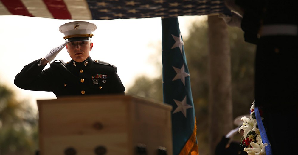Photo: U.S. Marine Corps/Cpl. Caitlin Brink -- Marines from Marine Corps Recruit Depot Parris Island's burial team salute the nation's flag as it is held over the casket of Medal of Honor recipient Capt. John James McGinty III.