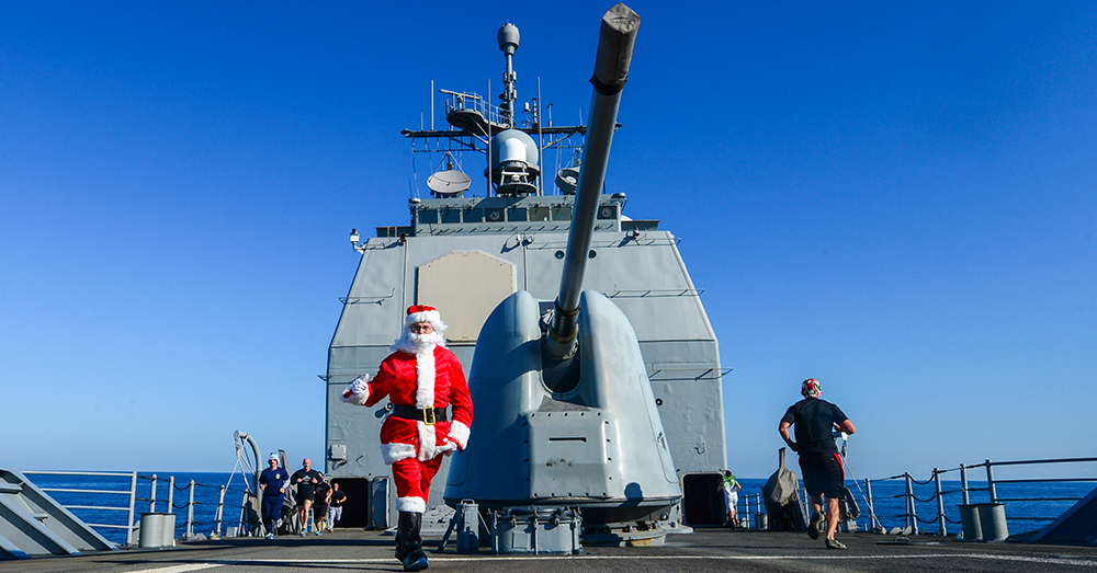 Photo: U.S. Navy/Mass Communication Specialist 2nd Class Billy Ho -- Cmdr. Darren Dugan, executive officer aboard the guided-missile cruiser USS Monterey (CG 61), dresses as Santa Claus to cheer for Sailors during a 5K run on the ship's foc'sle.