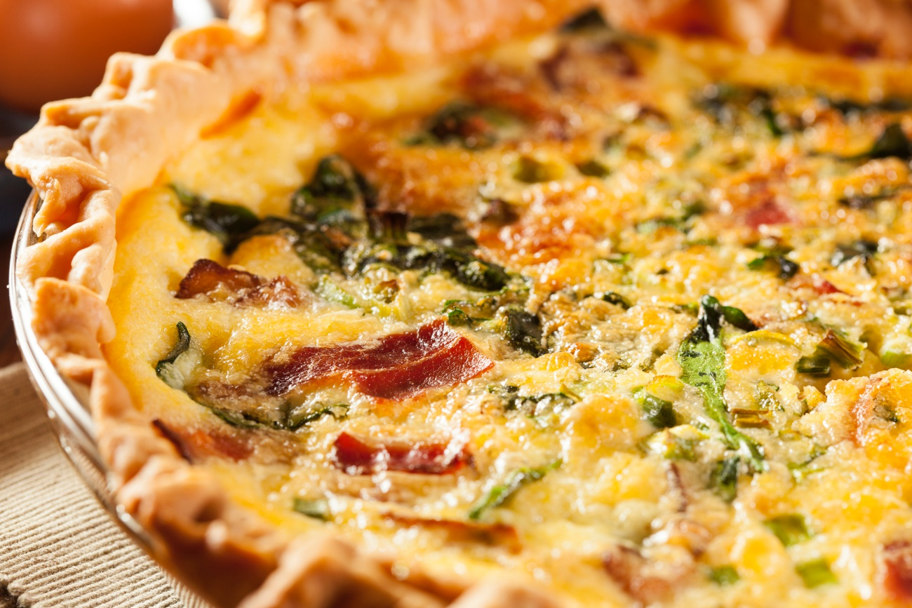 Close up of a quiche made from spinach, egg and bacon