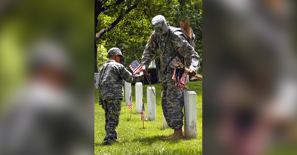 Father and son place flags for Arlington National Cemetery's