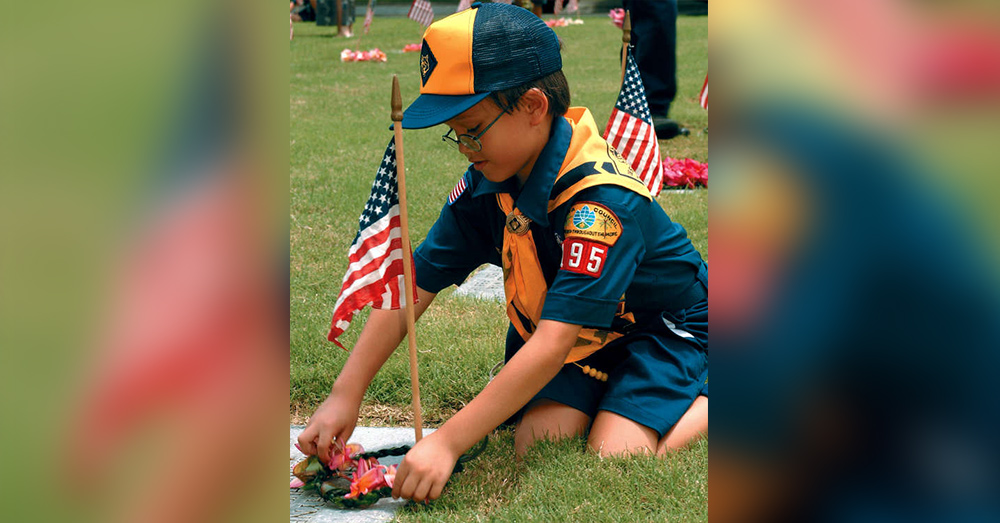 Cub Scout places a lei and flag on Memorial Day