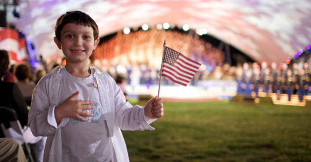 A young patriot waves the American flag at a Memorial Day concert