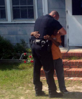 Young Cameron shares a hug with Sumter police officer Gaetano Acerra