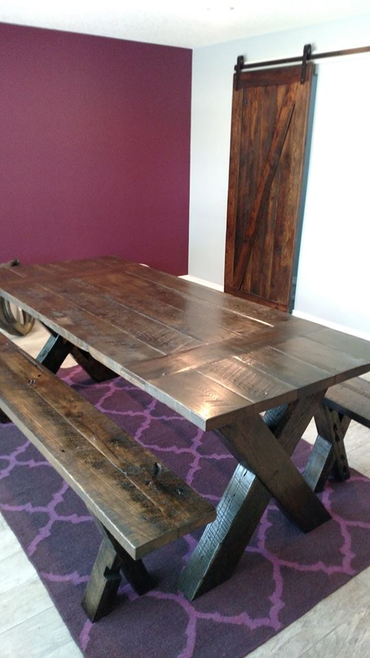 Custom oak dining table with inlayed walnut, benches, and custom sliding barn door all made from salvaged barnwood.