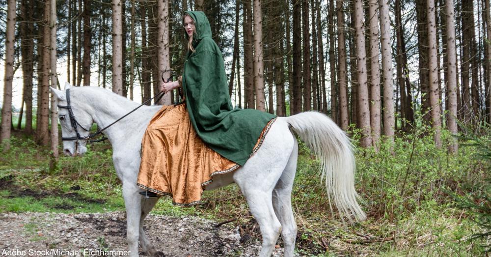 Reiterin in Mittelalterkostm auf Pferd vor Wald