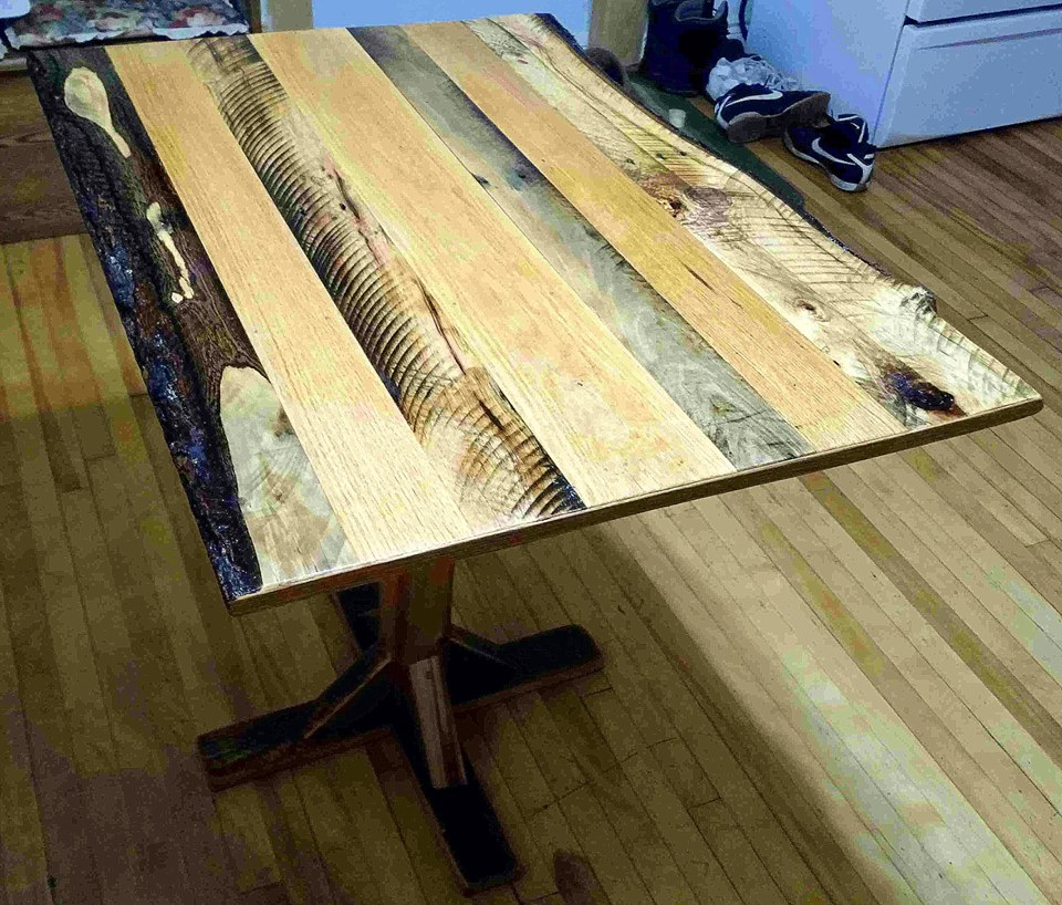From Anthony Kimber: This latest labor of love is truly a woodmutt: The feet are courtesy of a downed barn, The center post, was actually a jackpost, propping up my kitchen floor. The top a melange of alternating filthy pallet wood, and saintly oak strips from an abandoned church pew...HALLELUJAH! A table is born.