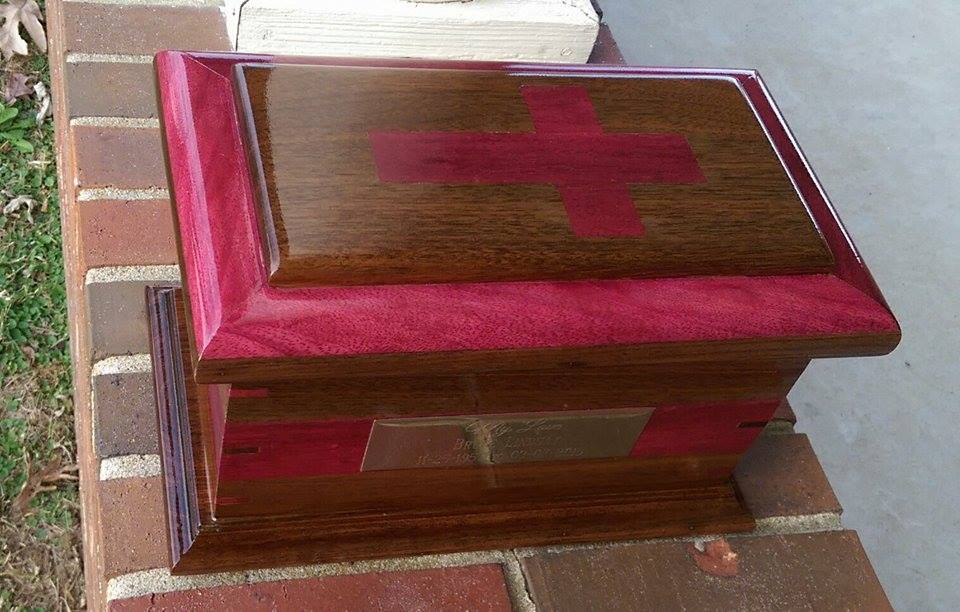 From Justin Fulton: I had the honor of making this crematory urn of walnut and purple heart. The lid has a double onlay and is inlaid with a cross. The body also has a wrapped Inlay and keyed miter joints of contrasting woods. This was my first inlay and first keyed miters.
