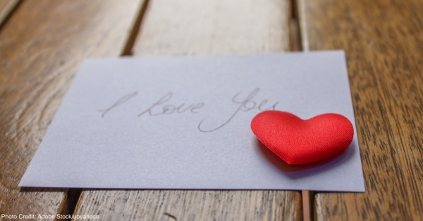 I love you note with a red love heart on a wooden surface