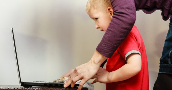 Little boy with laptop and mother helping.