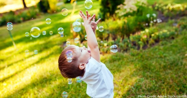 Little boy with soap bubbles in summer park.
