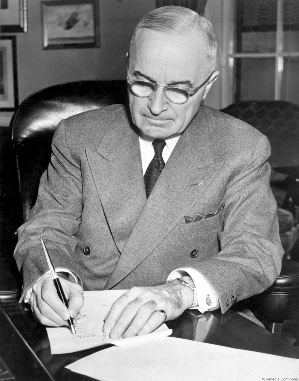 President Harry S. Truman is shown at his desk at the White House signing a proclamation declaring a national emergency.  December 16, 1950.