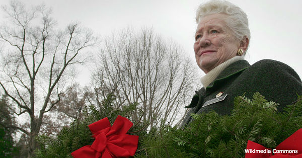 Betty J. Kelson of Army Arlington Ladies fights back tears as she carries two wreaths to place on graves during an annual holiday event to honor and remember veterans at Arlington National Cemetery, Dec. 15, 2007.
